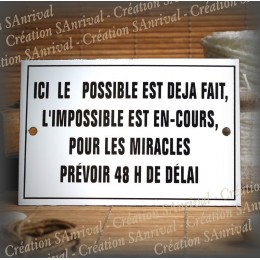 "Enamel plate with French text ""Ici le possible est déjà fait"""